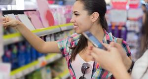 Frau im Supermarkt sucht Produkte aus